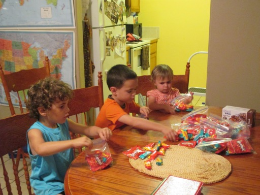 Ethan, Titus, and Nora preparing goodie bags to encourage the MKs in Oaxaca.