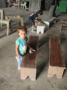 Tito and Nora helping to get the barn ready by  washing benches for the gathering